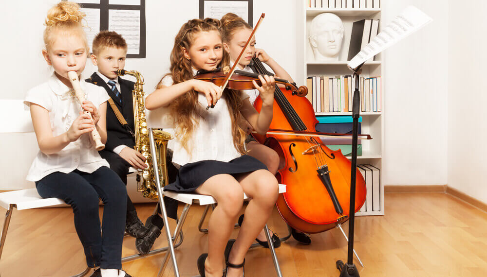 Group of kids learn how to play musical instruments.